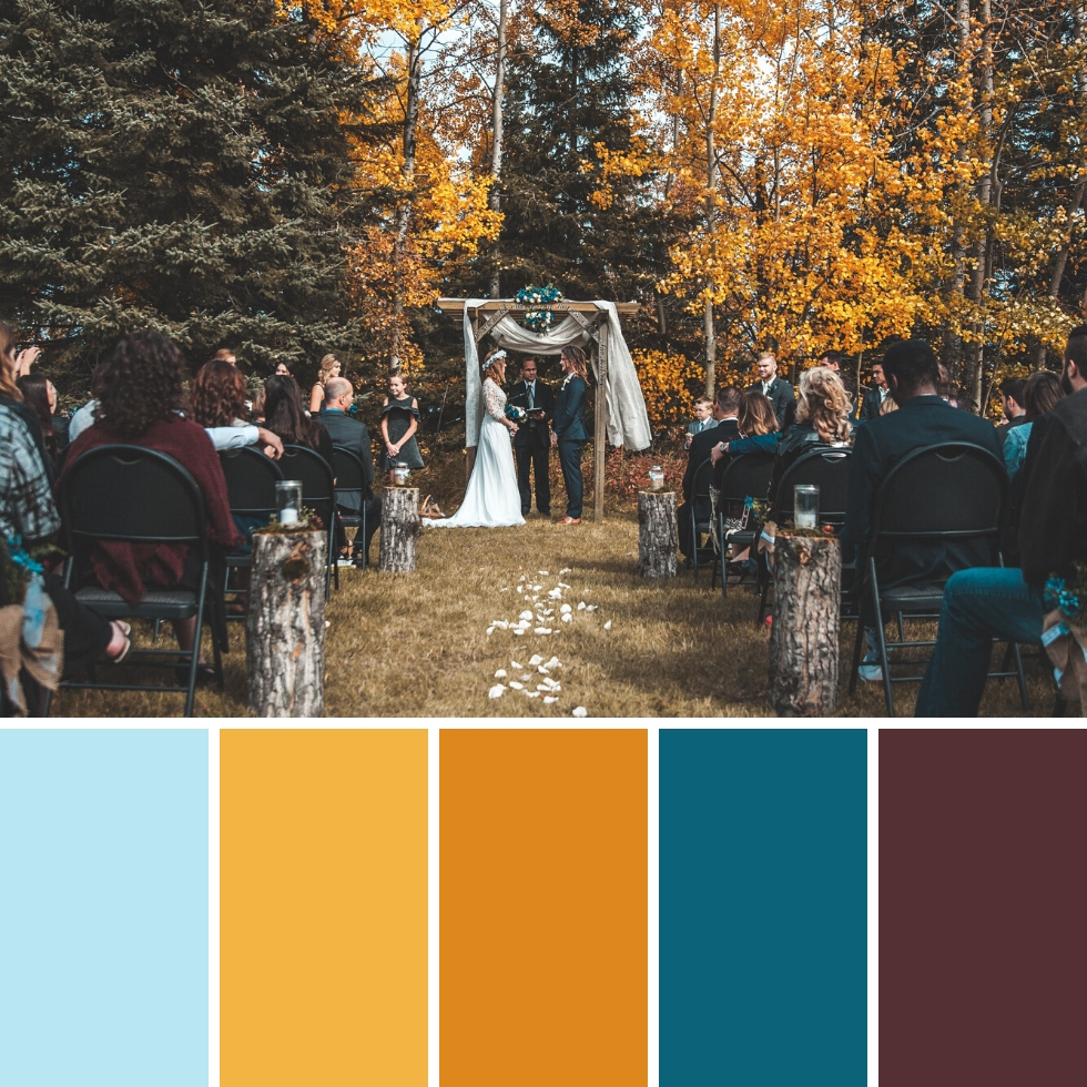 couple getting married outdoors surrounded by trees and loved ones autumn colour palette